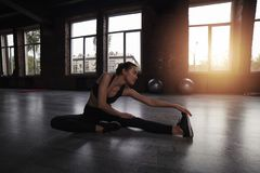 Athletic girl does stretching exercises at the gym. Determined athletic girl does stretching exercises at the gym royalty free stock image