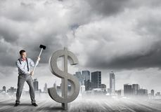 Determined banker man against modern cityscape breaking dollar concrete figure. Young furious businessman going to crash with hammer stone dollar symbol stock images