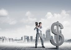 Determined banker man against modern cityscape breaking dollar concrete figure. Young furious businessman going to crash with violin stone dollar symbol royalty free stock photos