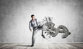 Determined banker man in empty concrete room breaking dollar fig Stock Photo
