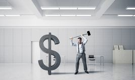 Determined banker man in modern office interior breaking dollar figure. Young furious businessman going to crash with hammer stone dollar symbol royalty free stock image