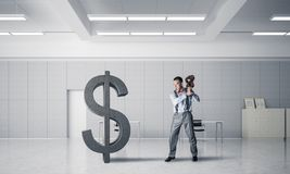 Determined banker man in modern office interior breaking dollar figure. Young furious businessman going to crash with violin stone dollar symbol royalty free stock image