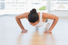 Determined beautiful woman doing push ups in gym Stock Photo