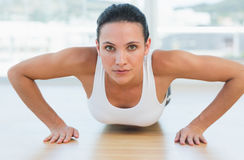 Determined beautiful woman doing push ups in gym Stock Images