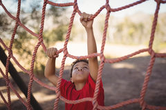 Determined boy climbing a net during obstacle course Royalty Free Stock Photography
