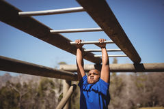 Determined boy exercising on monkey bar during obstacle course. In boot camp Royalty Free Stock Image