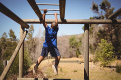 Determined boy exercising on monkey bar during obstacle course. In boot camp Royalty Free Stock Photo