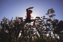 Determined boy jumping over obstacle. In boot camp stock photography