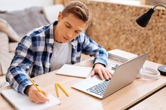 Determined boy learning his lessons at home. Learning lessons. Attractive serious fair-haired boy working on his laptop and writing in his notebook while sitting stock photo