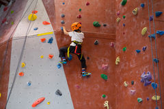 Determined boy practicing rock climbing. In fitness studio Royalty Free Stock Photos