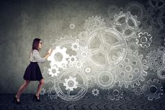 Determined business woman pushing gears royalty free stock image