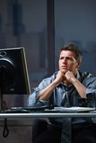 Determined businessman concentrating. Hard on difficult computer task working late in office looking worried Stock Photography
