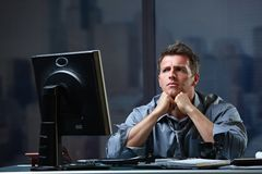 Determined businessman concentrating. Hard on difficult computer task working late in office looking worried Stock Images