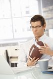 Determined businessman in office with football Royalty Free Stock Images