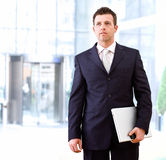 Determined businessman outdoor. Determined successful businessman standing and holding laptop computer in hand, outdoor in front of office building Royalty Free Stock Image