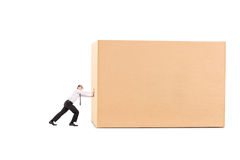 Determined businessman pushing a huge box Stock Photo