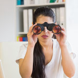 Determined businesswoman looking through binoculars Stock Photos