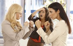 Determined businesswomen fighting at workplace. Young colleague watching it with fear from the background stock image