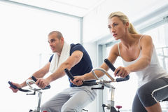 Determined couple working on exercise bikes at gym Royalty Free Stock Photos