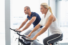 Determined couple working on exercise bikes at gym Royalty Free Stock Photography