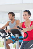 Determined couple working out at spinning class in gym Royalty Free Stock Photos