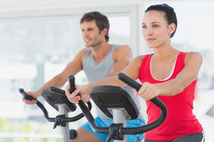 Determined couple working out at spinning class in gym Stock Image