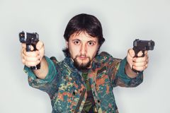 Determined criminal holding two guns Stock Photography