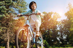 Determined energetic child heading somewhere. Going further than ever. Bright emotional clever kid exploring new places while reading his bicycle and wearing Royalty Free Stock Photography