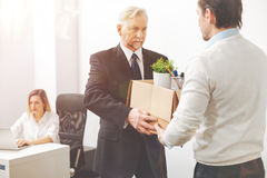 Determined enterprising executive asking his employee leaving the office. You are not welcome here. Solid persuasive mature men handing the worker his belongings Stock Photography