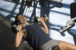 Determined Exercising With Dumbbells In Club. Determined man exercising with dumbbells in health club Royalty Free Stock Photo