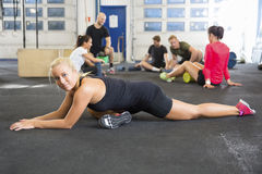 Determined Female Athlete Doing Stretching Exercise At Health Club Stock Photo