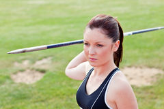 Determined female athlete ready to throw javelin. In a stadium stock photo