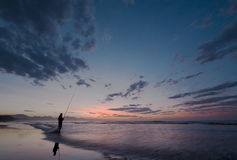 Determined fisherman. Very keen fisherman trying his luck at daybreak at the coastline near Mossel Bay in South Africa Royalty Free Stock Photo
