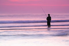 Determined fisherman.Sunrise. Sihouletted person surf fishing on a summer morning while standing in the  ocean water Stock Image
