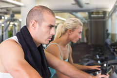 Determined fit couple working on exercise bikes at gym Royalty Free Stock Photography