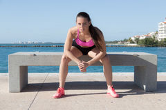 Determined, fit hispanic woman sitting on a bench Royalty Free Stock Images