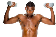 Determined fit shirtless man lifting dumbbells Royalty Free Stock Photography