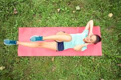 Determined fit young woman doing sit-ups in a park. Lying on a yoga mat, rising legs and head in the air. High angle view, directly from above. Active sport royalty free stock photography