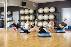 Determined Friends Exercising With Medicine Ball In Gym. Young determined male and female friends exercising with medicine ball in gym stock images