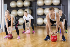 Determined Friends Lifting Kettlebells In Gym Royalty Free Stock Photos