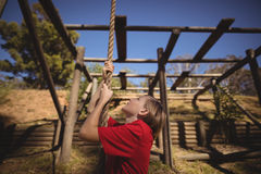 Determined girl climbing rope during obstacle course Stock Image