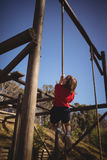 Determined girl climbing rope during obstacle courseDetermined girl climbing rope during obstacle co Royalty Free Stock Image