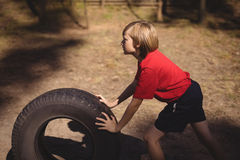 Determined girl exercising with huge tyre during obstacle course royalty free stock photos