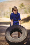 Determined girl exercising with huge tyre during obstacle course royalty free stock images