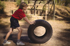 Determined girl exercising with huge tyre during obstacle course stock photography