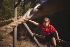 Determined girl exercising on outdoor equipment during obstacle course stock photos