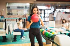 Determined Girl Getting Ready To Throw Bowling Ball At Alley. Determined teenage girl getting ready to throw bowling ball at alley in club stock photography