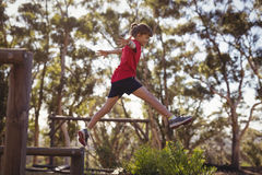 Determined girl jumping over obstacle. In boot camp royalty free stock photography