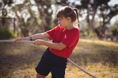 Determined girl practicing tug of war during obstacle course. In boot camp royalty free stock photography