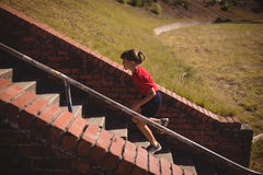 Determined girl running upstairs during obstacle course. In boot camp royalty free stock photography